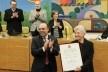 Rosa Kliass recebe o título de Cidadã Paulistana do vereador Police Neto, autor da iniciativa; ao fundo, Lucia Costa, autora do texto<br />Foto André Bueno  [CMSP]
