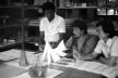 Professores Cirineu de Almeida (arquiteto), Sáida Cunha (pintora), e Tai Hsuan-An (arquiteto e pintor) avaliando trabalhos dos alunos na Escola de Artes e Arquitetura da PUC-Go, década de 1980<br />Foto Amaury Menezes