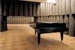 Joseph Beuys, Plight. Instalação com 43 elementos de feltro cinza com 5 rolos cada um, piano, quadro preto, termômetro, 3,10x8,90x13,15, Centre Georges Pompidou, Paris. [HUCHET, S. Intenções Espaciais. P. 210.]