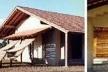 Figura 22 – À esquerda, foto mostrando fachada oeste da Casa Lar. Notar a pérgula, em paus roliços rústicos e a varanda na fachada sul. À direita, vista da pérgula do interior em fase final de construção. Notar abertura para ventilação próxima à cumeeira [Fotos cedidas pelo Arquiteto Severiano Mário Porto]