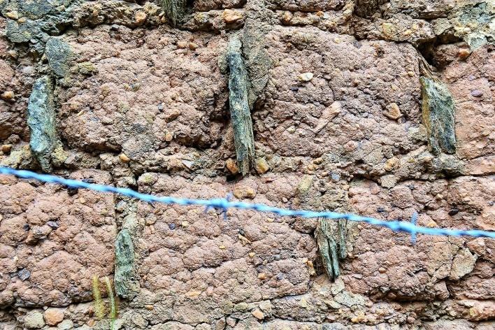 Seixos na composição dos tijolos de adobe e cacos de telha ou pedra entre os adobes, no muro de adobe retelhado e sem reboco, em Diamantina MG, 2014<br />Foto Elio Moroni Filho