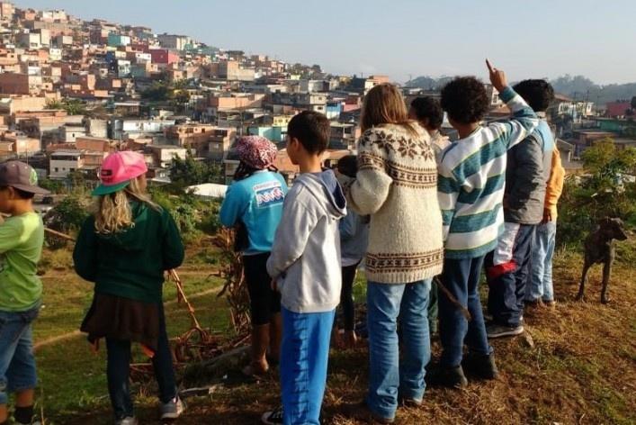 Antes da pandemia Covid-19, professora Carmen e alunos da Escola de Resiliência estão próximos a horta biodinâmica e observam a paisagem construída no Horizonte Azul<br />Foto William Rodrigues