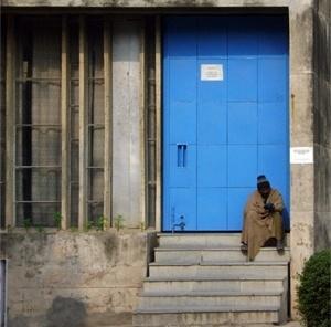 Homem sentado diante de prédio da universidade<br />Foto de Denise Teixeira e Luís Barbieri