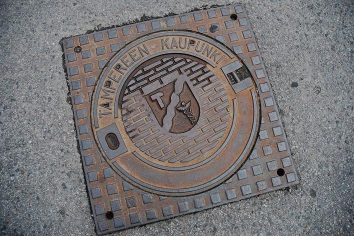 """Detalhe de infraestrutura urbana, tampa metálica com inscrição """"Tampereen Kaupunki"""" de caixa de passagem de sistema de captação de águas pluviais<br />Foto Fabio Lima"""