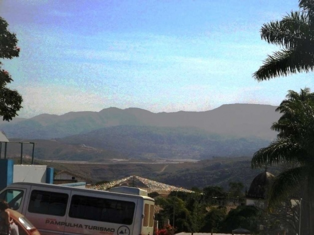 Montanhas diante do Santuário do Bom Jesus de Matosinhos, vendo-se, ao centro, uma das jazidas mineradoras, cuja incidência de poluição é notável sobre o conjunto do Santuário