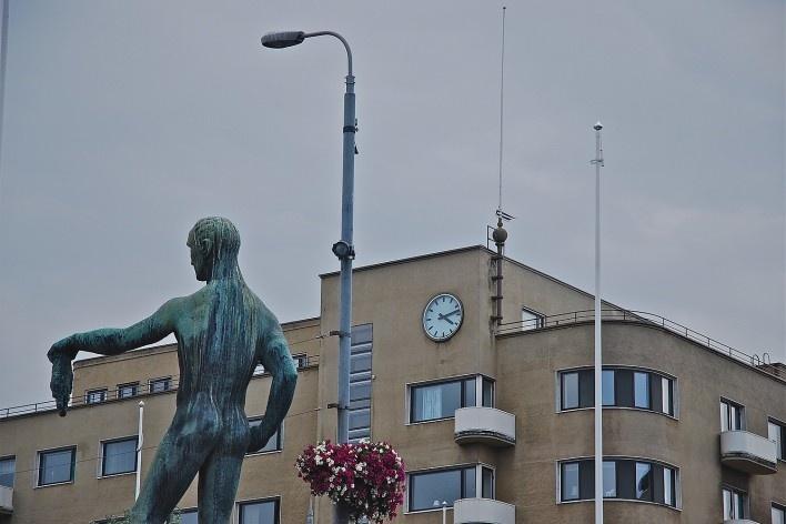 Arte urbana, escultura na Ponte Hämeensilta sobre o rio Tammerkoski no centro urbano com edificação preservada ao fundo<br />Foto Fabio Lima