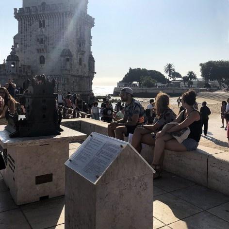 Totem com informações em Braille, maquete tátil e, ao fundo, a Torre de Belém, Lisboa<br />Foto Larissa Scarano, 2018