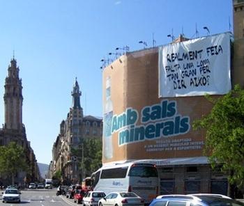 Intervenção anônima sobre lona publicitária em fachada de Barcelona<br />Foto Xico Costa