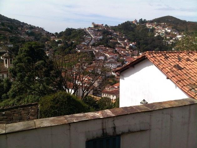 Casa com muro; ao fundo, caminho serpenteante na encosta<br />Foto Abilio Guerra