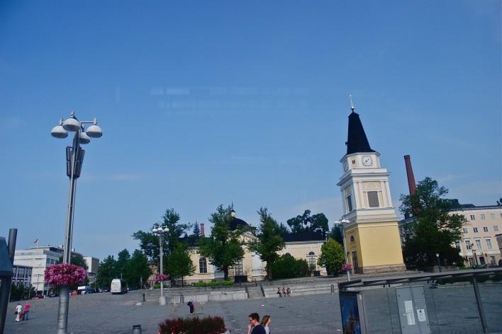 Ambiente refletido, aspecto do centro urbano com destaque para torre de igreja Vanha Tampereen Kirkko e chaminé de fábrica<br />Foto Fabio Lima