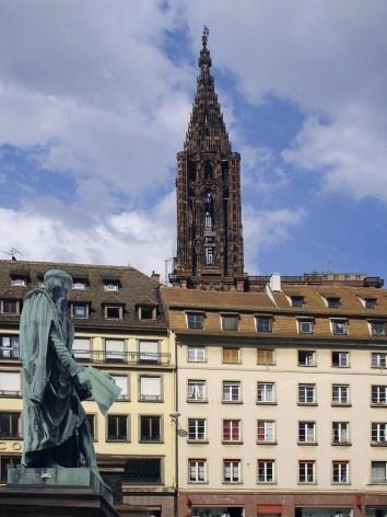 """Estátua de Gutenberg segurando nas mãos uma página do primeiro livro impresso em Mainz – a Bíblia – onde está escrito: """"Et la lumière fut""""; ao fundo, torre da Catedral de Notre-Dame de Strassbourg<br />Foto Victor Hugo Mori"""