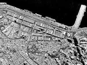 Figura 1 – Foto aérea (geral e zoom) da área portuária permitindo perceber o tecido urbano na região mais elevada, como ocupação predominante do século XIX e as áreas aterradas no início do século XX, ocupadas pelos galpões industriais [Acervo IPLAN-RIO]