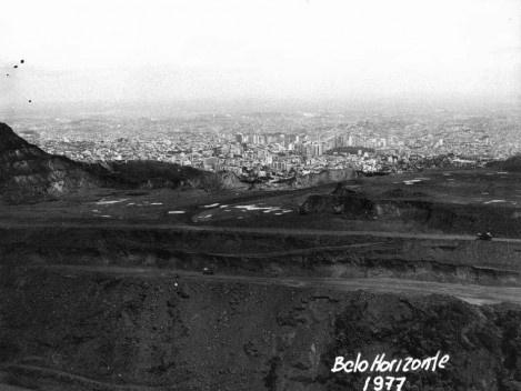 Fotografia tirada a partir da Serra do Curral que mostra mina de minério de ferro que foi explorada pela Ferrobel até 1979. Observa-se no canto superior esquerdo os taludes recortados pela atividade mineraria [Coleção José Góes, APM, 1977.]