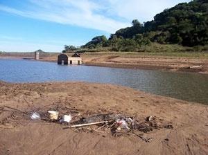 Vista parcial da Barragem do DNOS, 8m abaixo do nível normal, onde se observa o acúmulo de lixo no seu interior e a redução das potencialidades ambientais e paisagísticas<br />Foto autores, 2006