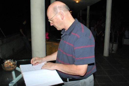 Guto Lacaz escrevendo no livro de dedicatórias da festa<br />Foto Thomas Bussius