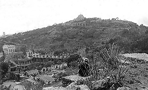 Fig. 4 - Provavelmente a foto mais antiga do Park Güell. Mostra o início das obras, com algumas mudas de palmeira já plantadas (esquerda, abaixo). Percebe-se o estado de degradação da encosta, com uma vegetação raquítica em meio às pedras [Cátedra Gaudí, Barcelona]