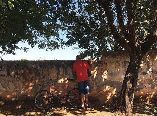 Homem com camiseta e bicicleta vermelhas observa sorrateiramente por cima do muro na Vila Xavier, em Araraquara<br />Foto Abilio Guerra, 27 maio 2018