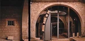 Páteo da Alfândega. À esquerda a epígrafe comemorativa da ampliação de 1432; ao centro a aduelas do arco do alpendre da torre medieval. <br />Fotografia: Ferreira Alves