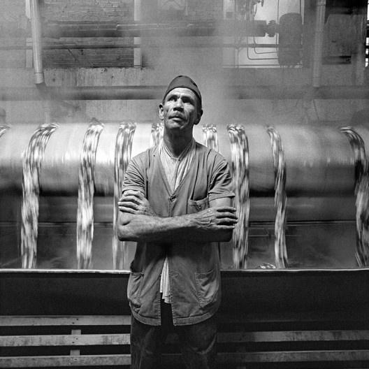 Tecelão de braços cruzados diante da máquina, São Paulo SP, 1975<br />Foto Cristiano Mascaro