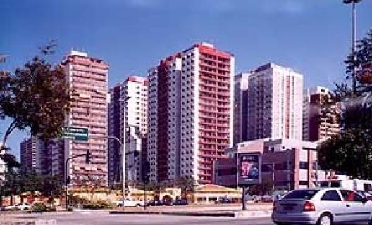 """Paisagem da Barra da Tijuca, com o paredão resultante das """"torres em meio ao verde"""", cada um em seu condomínio fortemente cercado, por detrás de faixa de comércio (shopping mall) e de via expressa, onde as distâncias são dificilmente precorridas por pedes"""