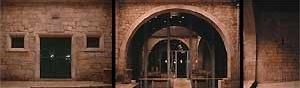 Páteo da Alfândega. À esquerda armazém principal da Alfândega (1677); ao centro aduelas de arco (séc. XV). <br />Fotografia: Ferreira Alves