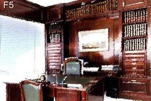 F5 – Nessa figura vê-se uma mesa de madeira. A cadeira mais afastada do observador é almofadada com tecido e tem espaldar mais alto do que a outra. Ao fundo, uma estante de madeira escura com um quadro no centro entre prateleiras de livros simétricas