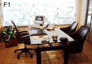 F1 – Aqui vê-se uma mesa com três cadeiras escuras, uma delas com espaldar mais alto, braços, rodas e elementos de regulagem. Sobre a mesa, objetos como monitor de tela plana, telefone e apoio de couro para escrever. Ao fundo, uma grande janela