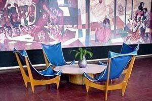 """Mobiliário de Joaquim Tenreiro para o Colégio de Cataguases (arquiteto Oscar Niemeyer). Ao fundo, detalhe do painel """"Tiradentes"""" de Cândido Portinari [Arquivo do Autor]"""